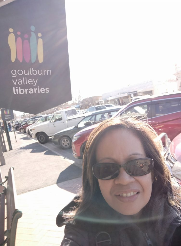 Female infront of Goulbourn Valley Libraries sign