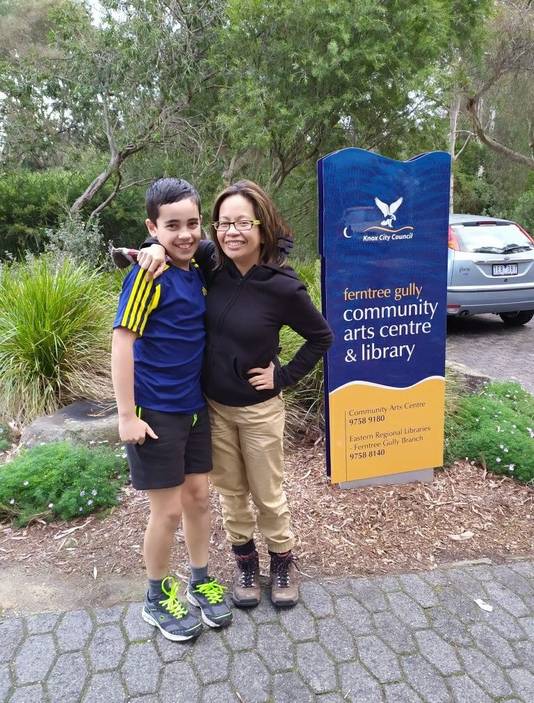 Mother and son smiling in front of a library sign